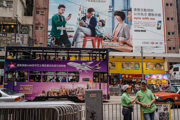 Hong Kong is a city of consumerism, full of ads and billboards. Sometimes it feels larger than life. May 2013, Causeway Bay. HongKong Urban Geometry City Consumerism Travel Street Street Photography Urban Travel Photography Strangers In Transit Sony RX1 Advertisement Billboard Showcase July Laif Photo Agency Jun Michael Park Pace Movement 35mm Urban Exploration