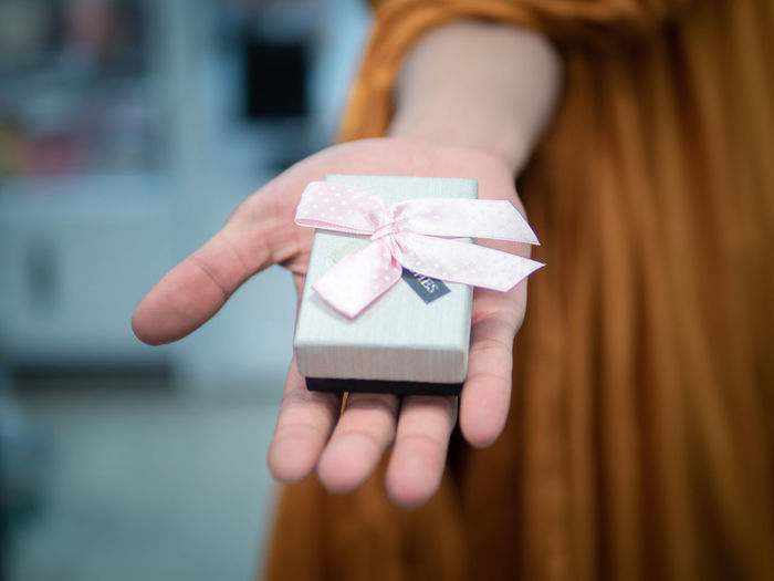 Close-up of woman hand holding gift at table