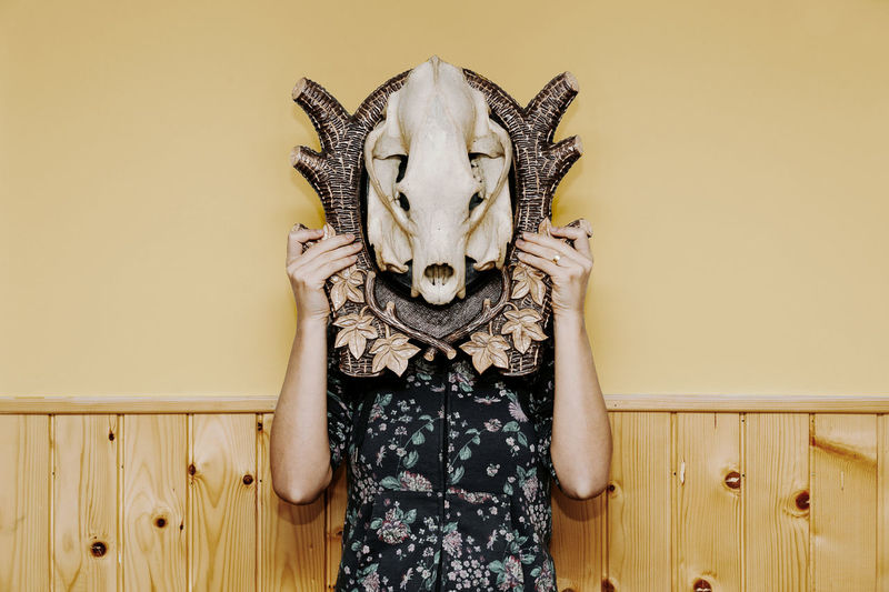 Woman with face covered by animal skull standing against wall