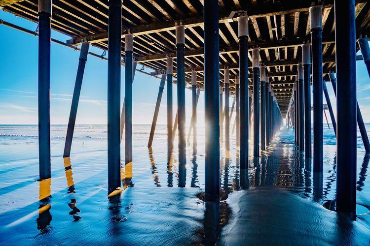 Pier over sea against blue sky