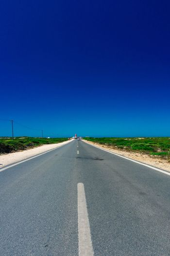 Country road against clear blue sky