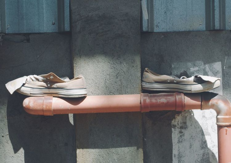 View of shoes on pipe against wall