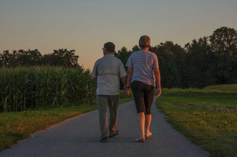 Rear view of friends walking on road amidst field against sky
