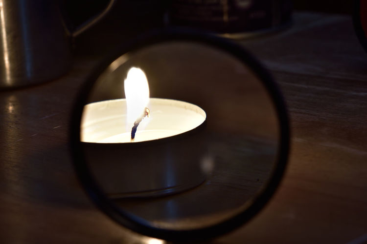 Close-up of lit tea light candle reflecting on mirror