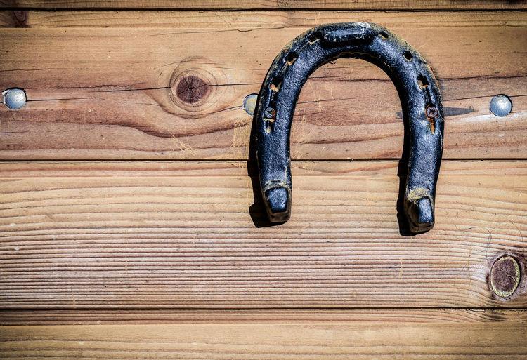 Close-up of horseshoe hanging on wood