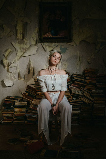 Portrait of young woman sitting on stacked books against weathered wall