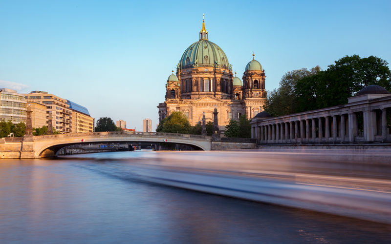 Blurred motion of boat in spree river by berlin cathedral at night