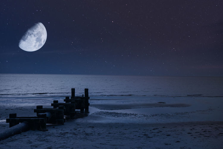 A night sky with a half moon and stars over the beach and ocean with a pipe