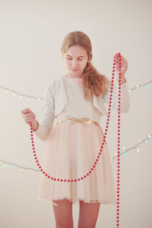 Portrait of young girl unwrapping red Christmas decorations Celebration Child Childhood Christmas Christmastime Decorate Decoration Decorations Dress Elegant Girl Hanging Out Happy Holiday Home Joy Lifestyles Light Ornament Person Smiling Teenager Tradition Unwrapping Young