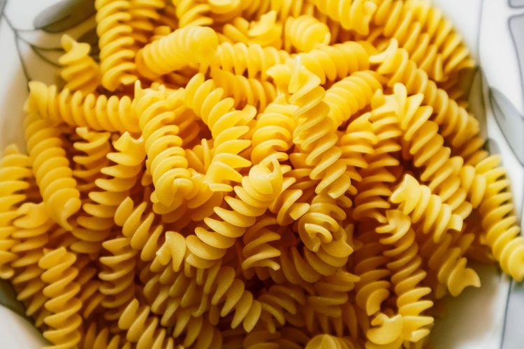 High angle view of yellow pasta in plate Cooking Dinner Food Lunch Macaroni Pasta Tagliatelle Carbohydrate Delicious Dry Health Ingredients No Person Noodles Nutrition Penne Spaghetti Traditional Uncooked Wheat Food And Drink Freshness Close-up Yellow Italian Food Indoors  No People Still Life High Angle View Abundance Wellbeing Raw Food Spiral Healthy Eating Indulgence Large Group Of Objects Plate Design Sweetcorn Temptation
