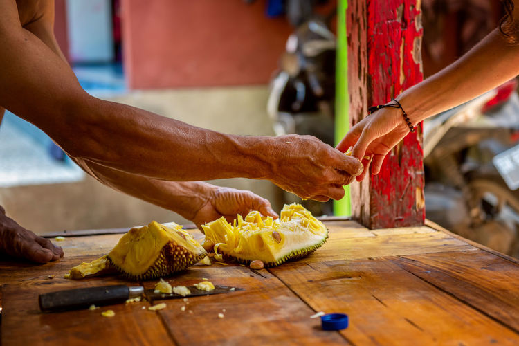 Photo of hands of balinese man cut exotic fruit durian in his house and share with tourist. bali