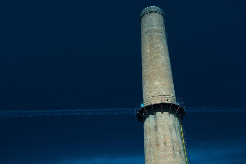 Low angle view of smoke stack against sky at night
