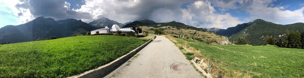 Panoramic view of road amidst landscape against sky