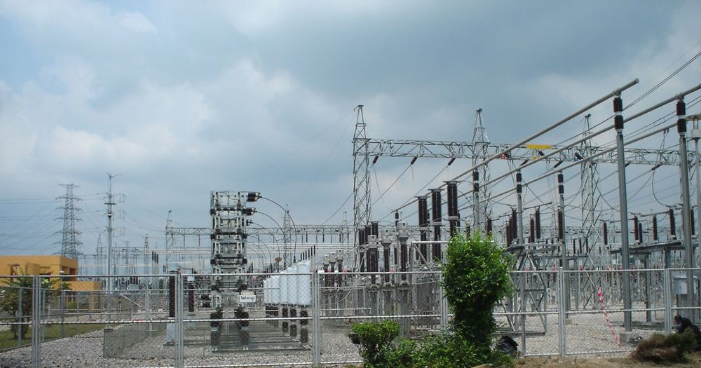 Electricity pylon by buildings against sky