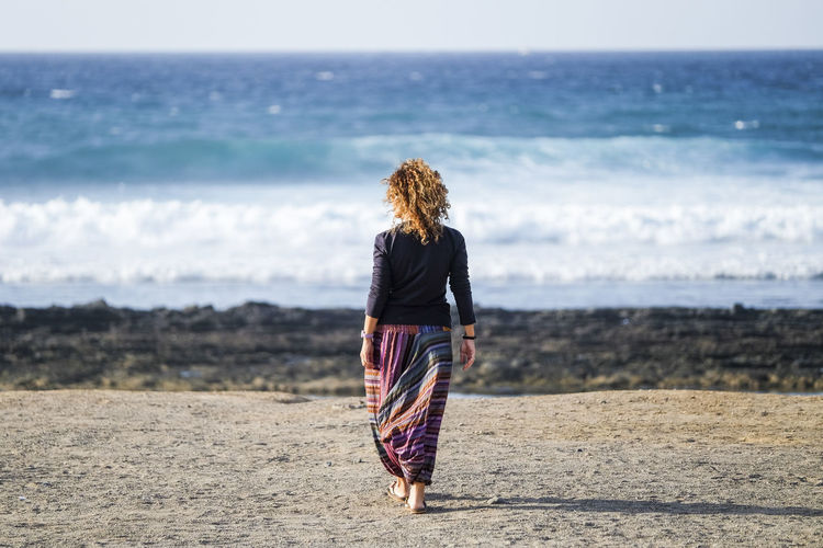Rear view of woman walking at beach during sunny day