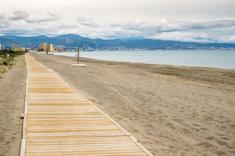 wooden promenade on the empty beach Wooden Promenade On The Empty Beach Promenade Beach Water Sky Cloud - Sky Land Sea The Way Forward Direction Scenics - Nature Mountain Nature Tranquil Scene Tranquility Wood - Material Day Beauty In Nature Sand Boardwalk Mountain Range Outdoors No People