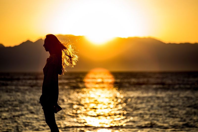 Silhouette woman standing by sea against orange sky