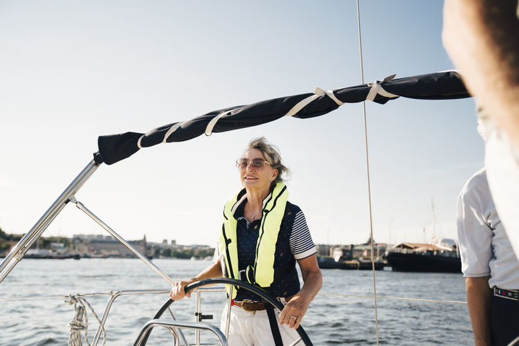 Woman standing on sailboat against sea against clear sky