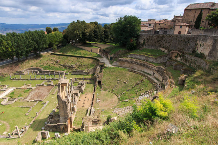 Ruined Of Ancient Roman Theater With Trees And Houses