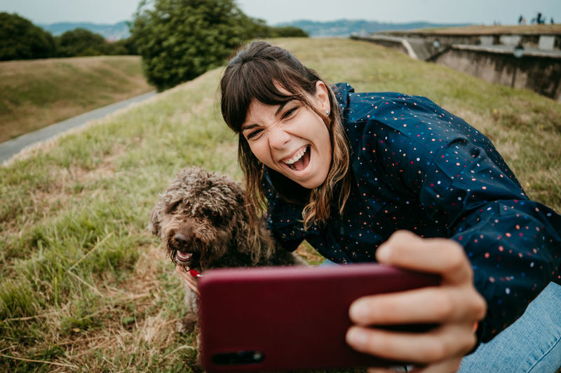 Woman taking selfie with dog on field