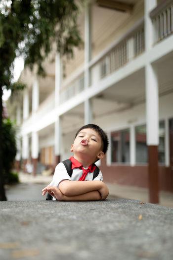 Portrait of cute boy sitting by school building