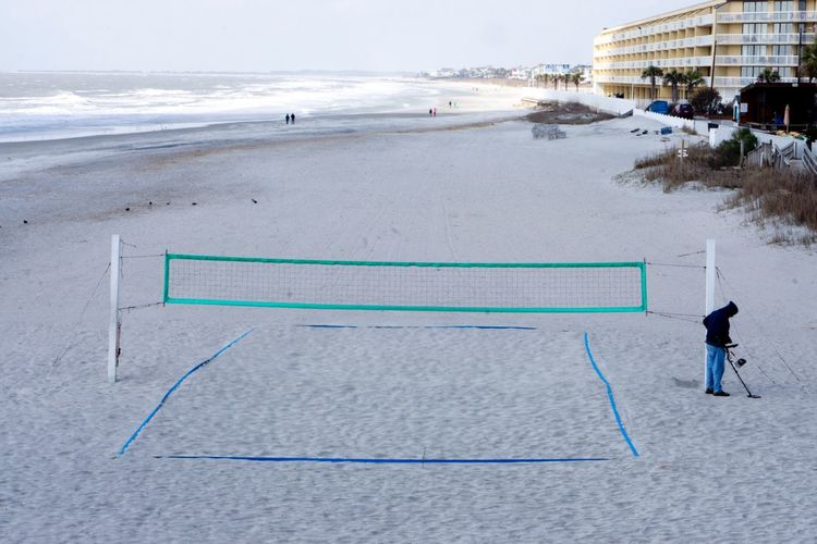High angle view of man standing by volleyball net at beach