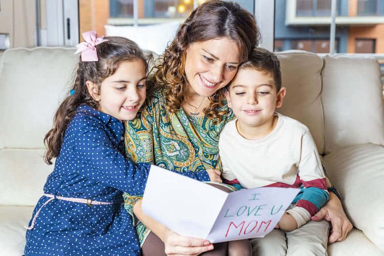 Mother with children holding greeting card with text on sofa in living room at home