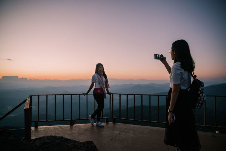 Woman photographing on railing against sky during sunset