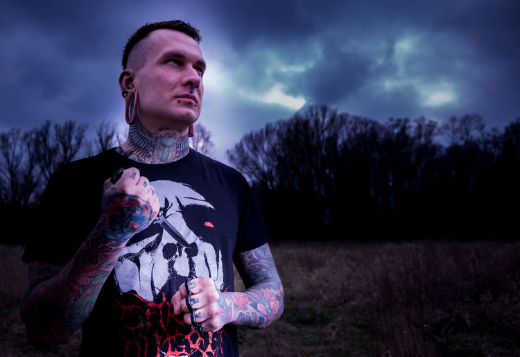 Tattooed man holding knife while standing on field against sky at dusk