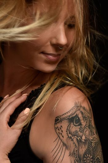 Young woman with cat tattoo One Person Lifestyles Tattoo Leisure Activity Real People Young Adult Young Women Beautiful Woman Blond Hair Indoors  Studio Shot Black Background Close-up AMP PICTURES
