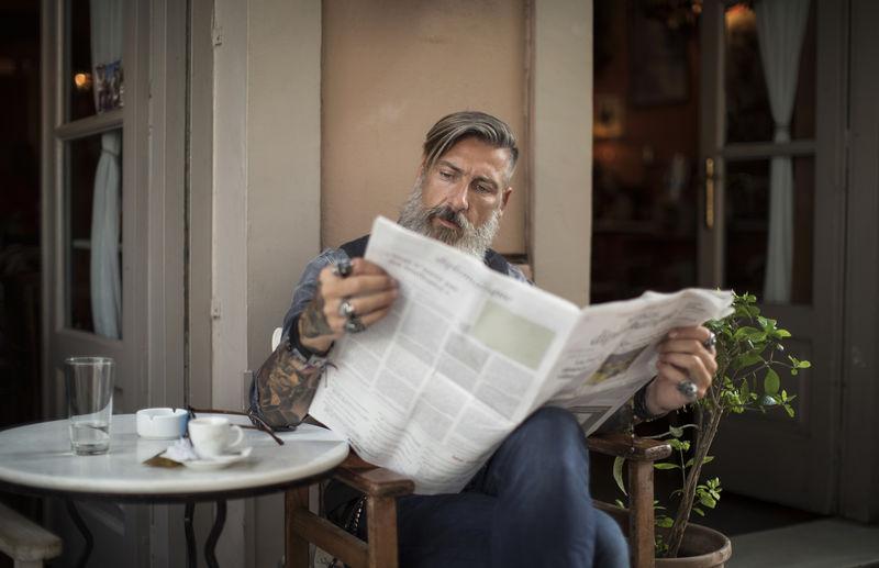 Mature Man Reading Newspaper While Sitting At Sidewalk Cafe