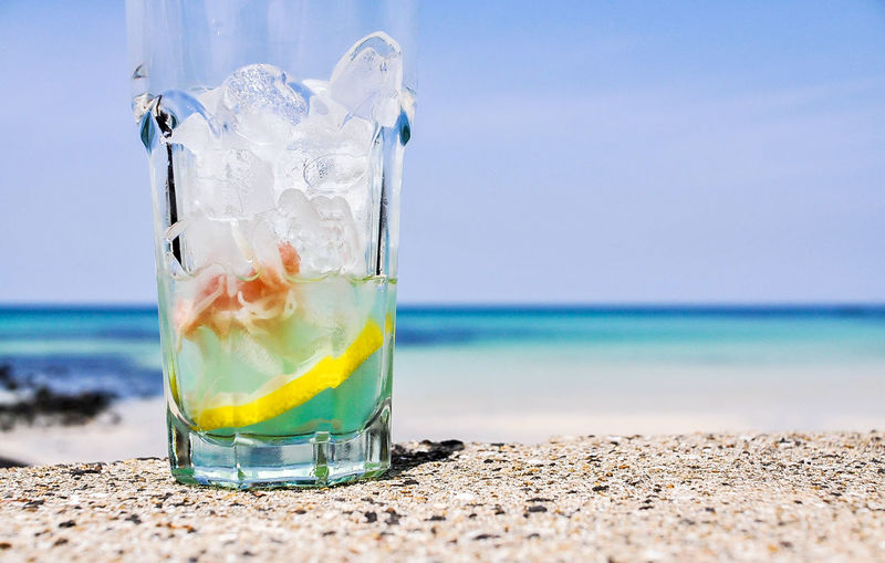 Close-up of drink at beach against sky