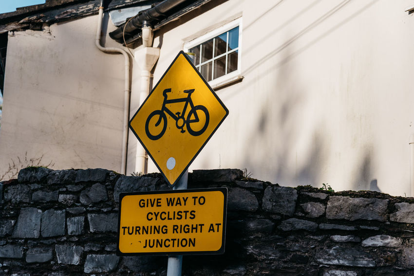 Traffic sign in the street of Cork Cork Cyclist Signal Travel Wild Atlantic Way Architecture Brick Building Exterior Built Structure Communication Day Guidance Information Information Sign Irish Kerry Landscape No People Outdoors Road Sign Script Sign Symbol Text Tourism Traffic Sign Wall Wall - Building Feature Warning Sign Warning Symbol Western Script Yellow