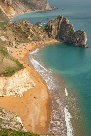 A high up view of the famous limestone arch Durdle Door and golden sand beach from the South West Coastal Path running on top of the near by cliffs, Lulworth Estate, Dorset, England. Durdle Door Jurrasic Coast Arch Bay Beach Beauty In Nature Coastline Day High Angle View Idyllic Land Limestone Nature No People Outdoors Rock Rock - Object Rock Formation Scenics - Nature Sea Solid Tranquil Scene Tranquility Water
