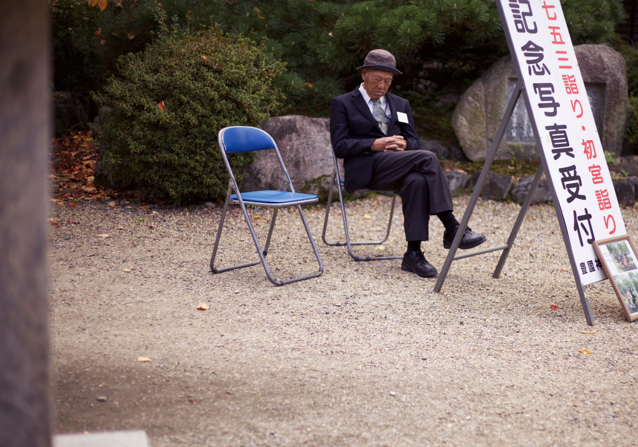 full length, sitting, chair, one person, communication, outdoors, front view, one man only, suit, day, tree, well-dressed, real people, men, only men, adult, adults only, people