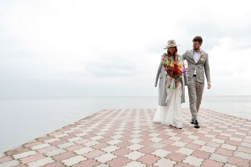 Newly Married Couple Walking On Pier Over Lake Against Cloudy Sky