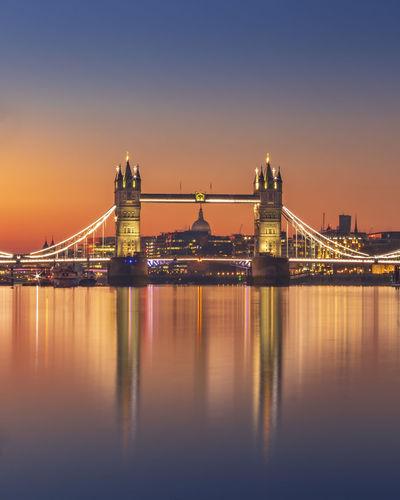 Illuminated bridge over river in city against sky
