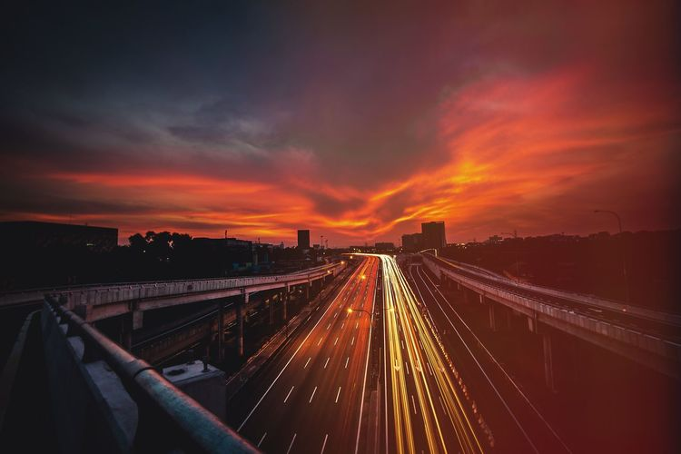 High Angle View Of Light Trails On Highway During Sunset