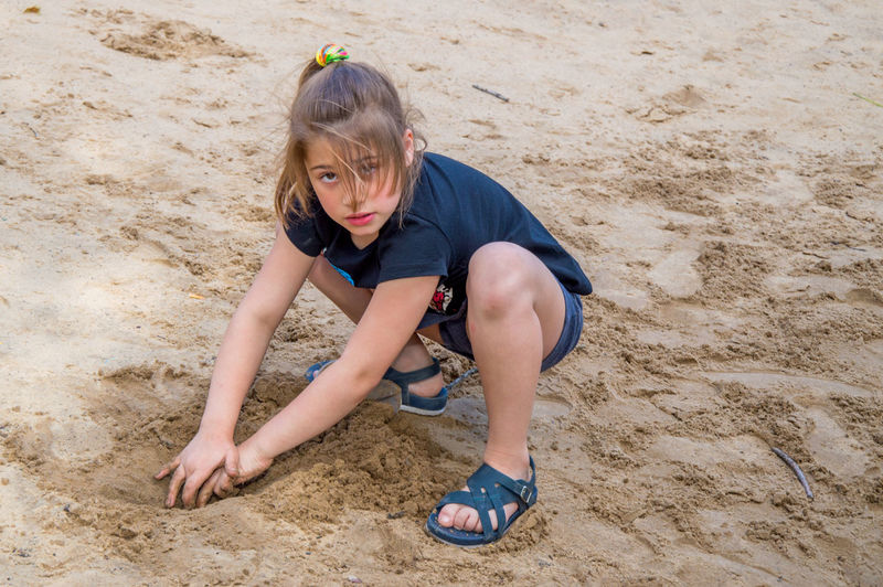 Portrait Of Girl Playing On Sandy Beach