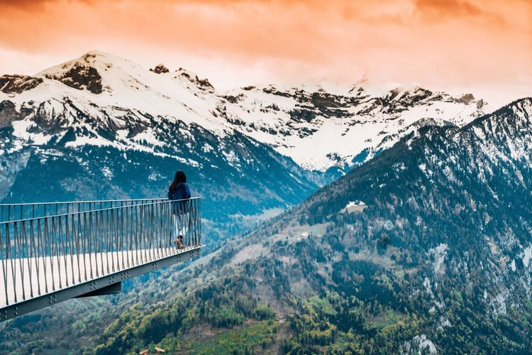 Woman looking at snowcapped mountains against sky