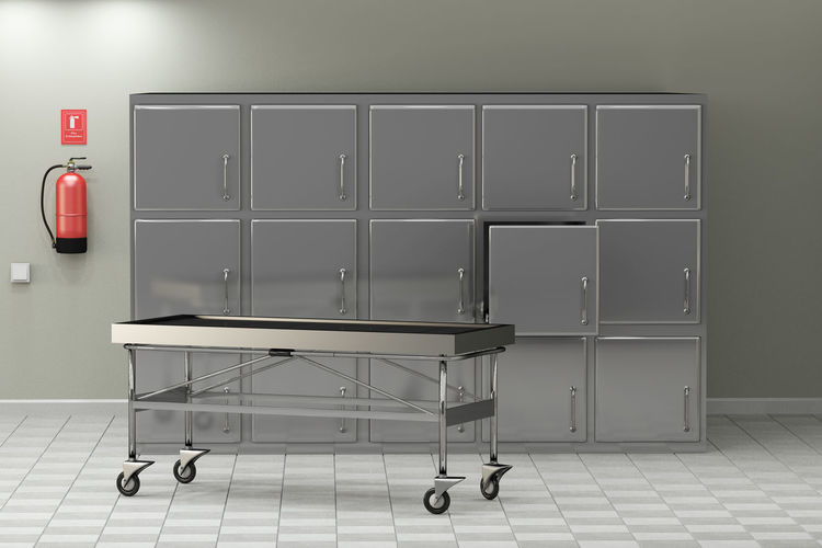 Stretcher On Floor Against Metallic Cabinets In Hospital