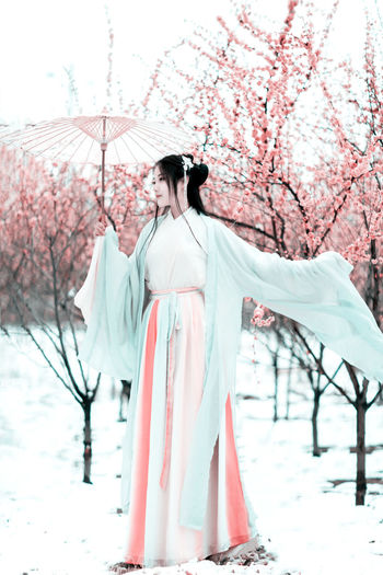 Young Woman Under Umbrella Standing Against Cherry Tree
