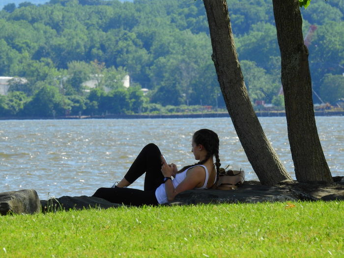 Side view of couple sitting on grass by lake against trees