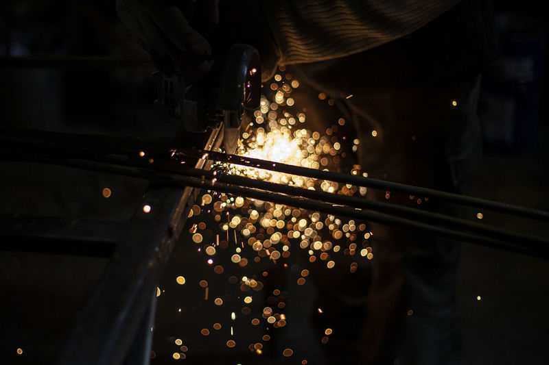 Cropped hand of person using grinder in factory