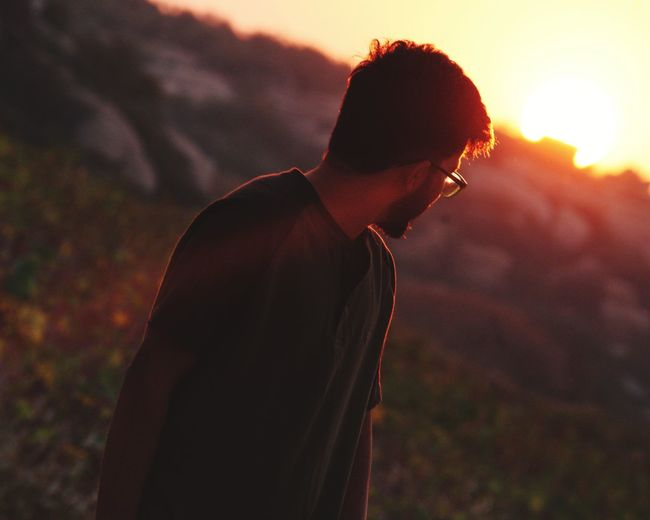 Side view of young man looking at sunset