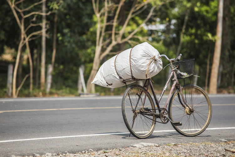 Sack tied to bicycle parked on road