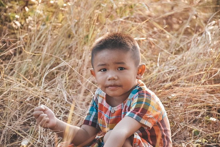 Portrait of cute boy sitting on field