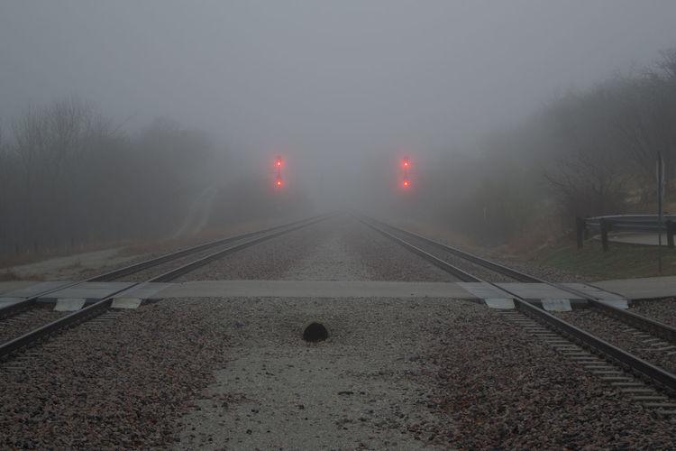 Train tracks receding into distance on a foggy day Fog Foggy Day No People Outdoors Signals The Way Forward Train Tracks Transportation