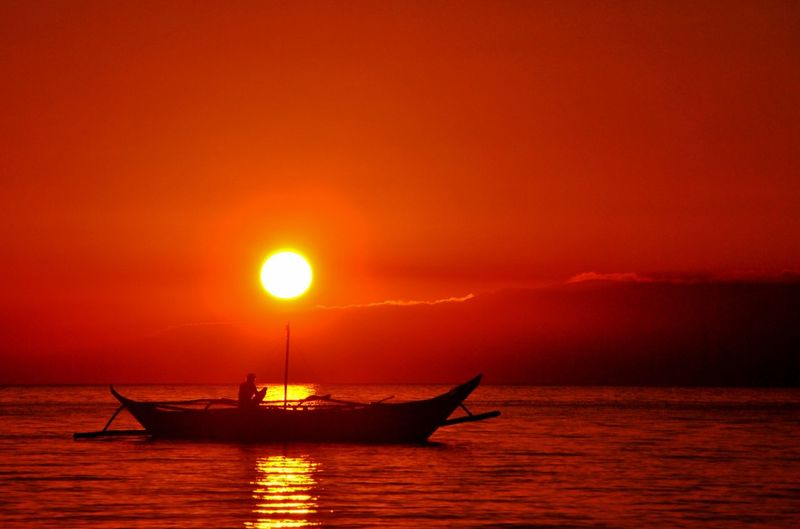 Sunset in Calatagan, Batangas Sunset Silohuette Orange Color One Man Only Fishing Boat Mountain Range Water Sky Sun Sea Tranquil Scene Beauty In Nature Idyllic Outdoors Reflection Scenics - Nature Travel