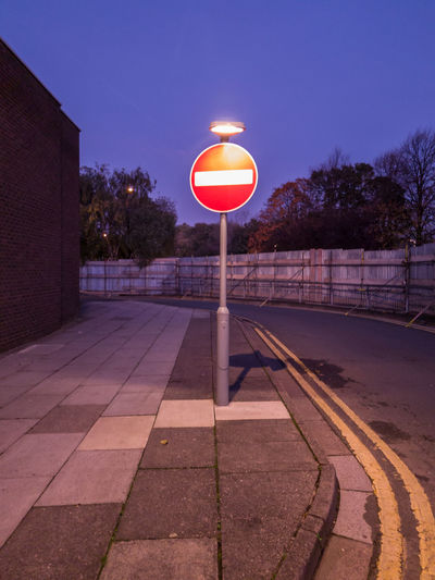 Illuminated road sign on footpath by street against sky